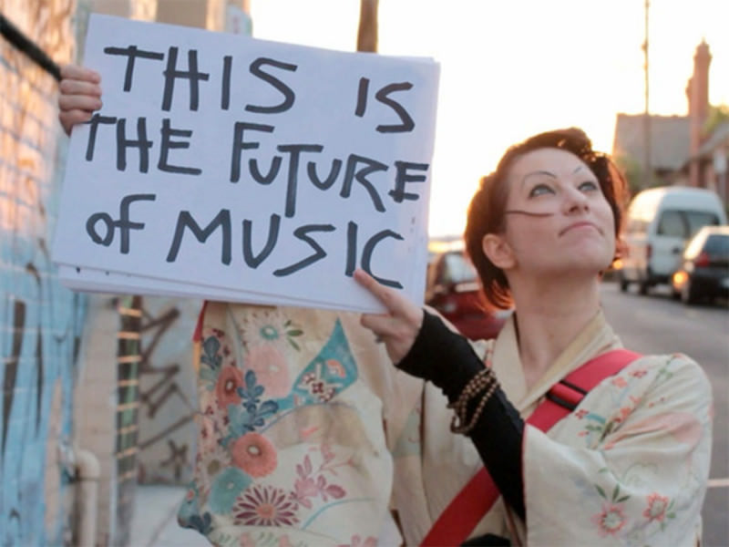 Amanda Palmer holds up a sign reading 'This Is The Future Of Music'