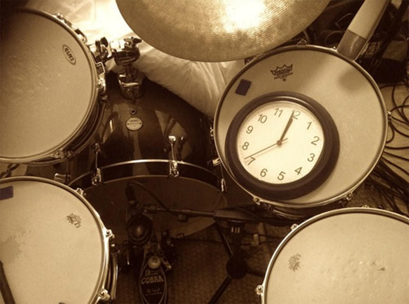 A clock showing midnight, lying on The Bedlam Six drum kit